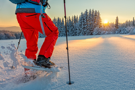 Detail of snowshoe walker in mountains with beautiful sunrise light. Outdoor winter activity and healthy lifestyle Stock Photo