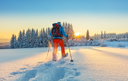 Snowshoe walker running in powder snow with beautiful sunrise light. Outdoor winter activity and healthy lifestyle Stok Fotoğraf
