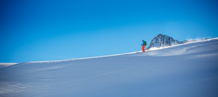 freerider: Freerider skier running downhill in beautiful Alpine landscape. Fresh powder snow, blue sky on background.