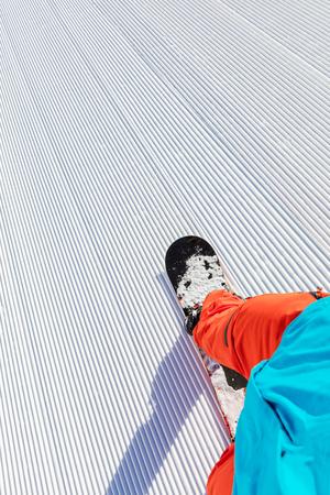 Detail of snowboarder running downhill on piste