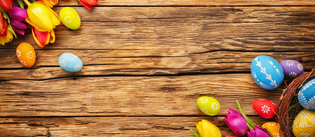 Easter eggs with tulips on wooden board, easter holiday concept. Copyspace for text.