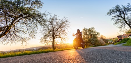 Motorcycle driver driving in beautiful sunset light Standard-Bild