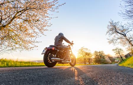Vista trasera del conductor de la motocicleta en la conducción hermosa puesta de sol Foto de archivo - 70587274