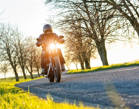 Motorcycle driver driving in sunset, blur grass on foreground Stock Photo