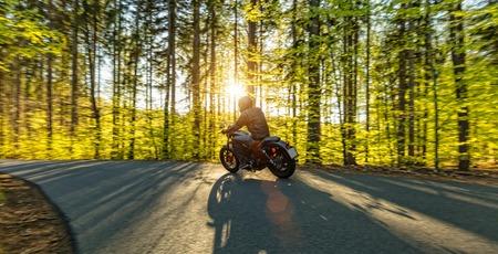 Conducteur de moto conduite dans la forêt, beau coucher de soleil Banque d'images - 70587276