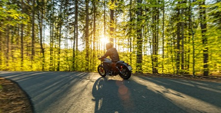 Motorcycle driver driving in forest, beautiful sunset