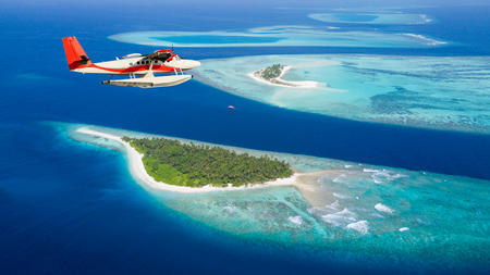 Sea plane flying above Maldives islands, concept of travel and vacation Banco de Imagens