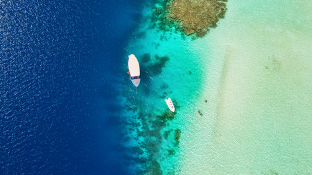 Beautiful coral reef in shallow water with anchoring boats, aerial view.