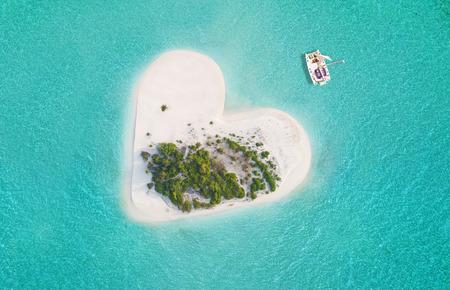 美しいハート形の小さな熱帯の島、カタマラン ボートでアンカリングします。