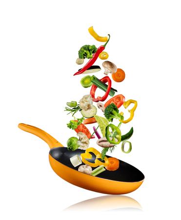 Verse groenten die in een pan vliegen, geïsoleerd op een witte achtergrond