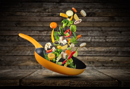 Fresh vegetables flying into a pan, placed on wooden planks