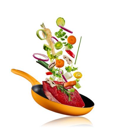 Verse groenten met biefstuk vliegen in een pan, geïsoleerd op een witte achtergrond