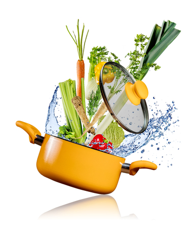 Fresh vegetables flying into a pot with water splash, isolated on white background Stock Photo
