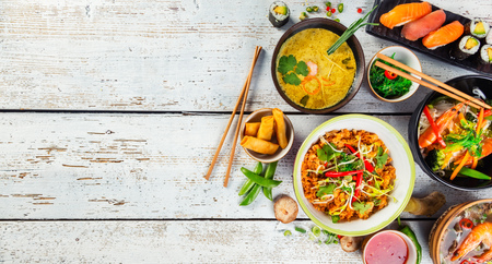 Asian food served on white wooden table, top view, space for text. Chinese and vietnamese cuisine set. Archivio Fotografico