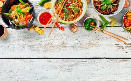 vietnamese: Asian food served on white wooden table, top view, space for text. Chinese and vietnamese cuisine set. Stock Photo
