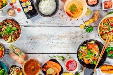 Asiatische Küche serviert auf weißen Holztisch, Ansicht von oben, Platz für Text. Chinesische und vietnamesische Küche gesetzt. Standard-Bild