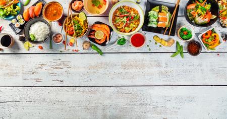 Asiatische Küche serviert auf weißen Holztisch, Ansicht von oben, Platz für Text. Chinesische und vietnamesische Küche gesetzt. Lizenzfreie Bilder