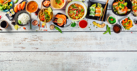 Asian food served on white wooden table, top view, space for text. Chinese and vietnamese cuisine set. Banque d'images