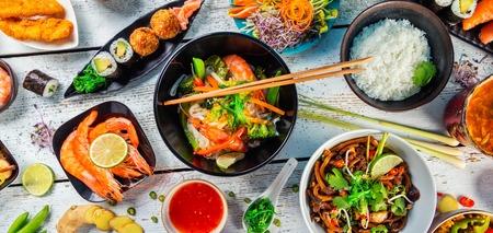 Asiatisches Essen serviert auf weißen Holztisch, Ansicht von oben. Chinesische und vietnamesische Küche gesetzt.