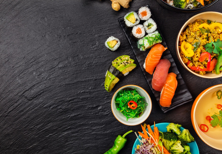 Asian food served on black stone, top view, space for text. Chinese and vietnamese cuisine set. Stockfoto