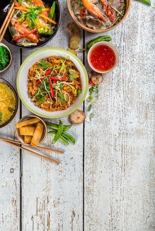 Aziatische gerechten geserveerd op een witte houten tafel, bovenaanzicht, ruimte voor tekst. Chinese en Vietnamese keuken set. Stockfoto - 72504511