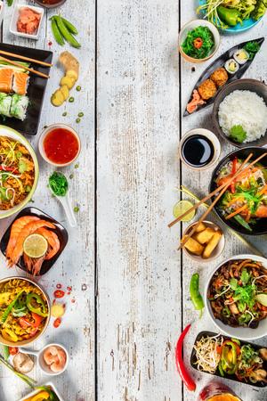 Aziatische gerechten geserveerd op een witte houten tafel, bovenaanzicht, ruimte voor tekst. Chinese en Vietnamese keuken set. Stockfoto - 72504497