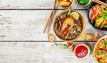 Aziatische gerechten geserveerd op een witte houten tafel, bovenaanzicht, ruimte voor tekst. Chinese en Vietnamese keuken set. Stockfoto