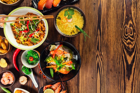 food table: Asian food served on old wooden table, top view, space for text. Chinese and vietnamese cuisine set.