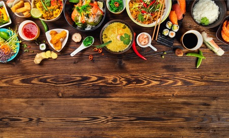 Asian food served on old wooden table, top view, space for text. Chinese and vietnamese cuisine set.