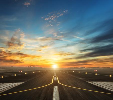 Pista dell'aeroporto nella luce del tramonto della sera, pronta per l'atterraggio o il decollo dell'aeroplano Archivio Fotografico - 72789839