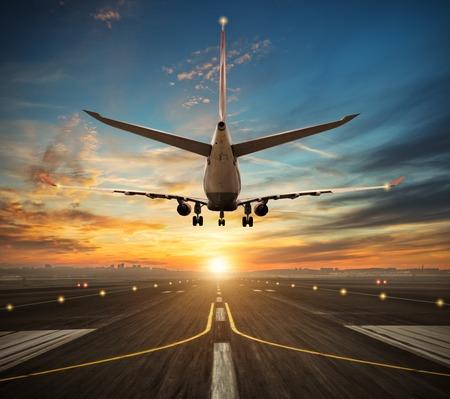 乗客航空機の美しい夕日の光、背景に近代的な都市のシルエットで空港の滑走路に着陸