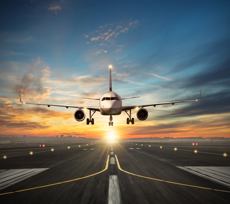 Passengers airplane landing to airport runway in beautiful sunset light, silhouette of modern city on background Standard-Bild