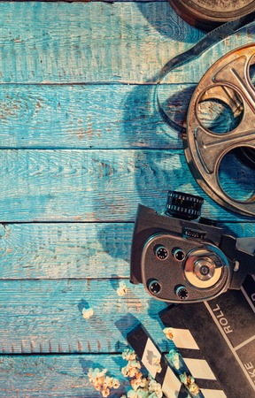 Film camera, roll and popcorn on wooden planks. Copyspace for text