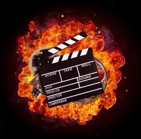 Film batacchio, bobina e fotocamera a fuoco, isolato su sfondo nero. Concetto di cinema. Archivio Fotografico - 73303789