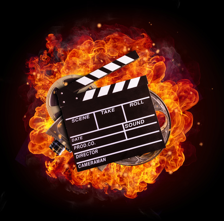 Film clapper, reel and camera in fire, isolated on black background. Concept of filmmaking.