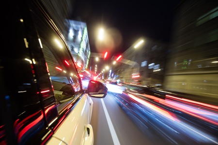 accelerated: Detail of car driving in city at night, blur motion