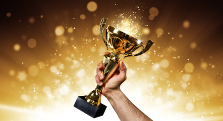 Man holding up a gold trophy cup with abstract shiny background, copy space for text