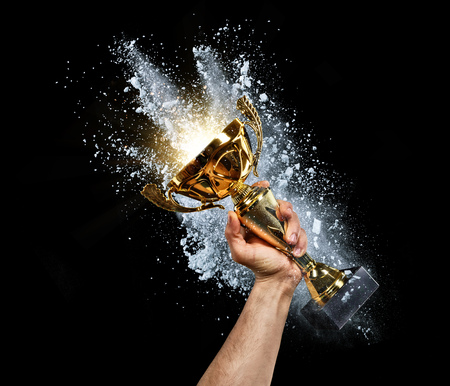 Man holding up a gold trophy cup with powder explosion on background. Concept of success and achievement. isolated on black background