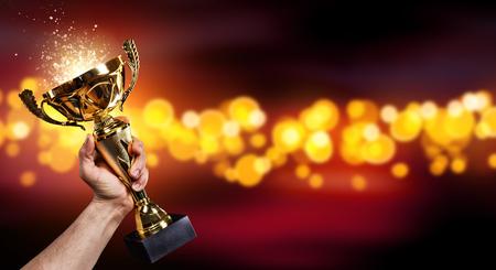 Homme tenant une tasse de trophée d'or avec un fond brillant abstrait, copiez l'espace pour le texte Banque d'images - 73559724