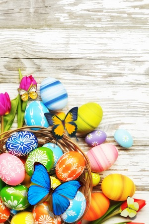 Easter eggs with tulips and butterfly on wooden board. Copyspace for text Stock Photo - 73791237