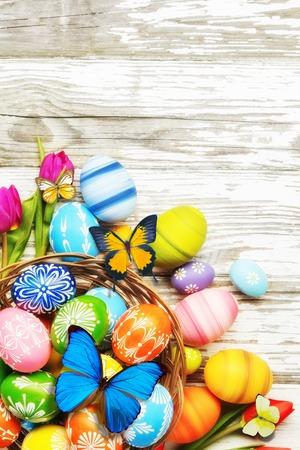 Ostereier mit Tulpen und Schmetterling auf hölzernem Brett. Exemplar für Text Standard-Bild - 73791237