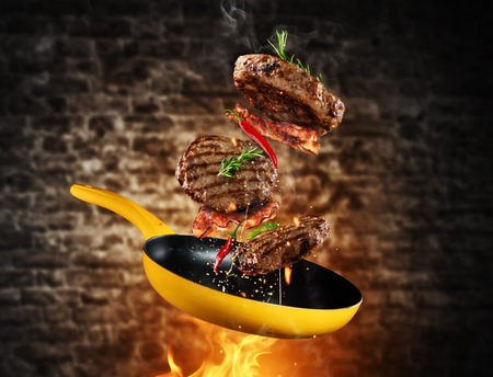 Beef milled meat flying from a pan with flames, grunge old brick wall on background Banco de Imagens