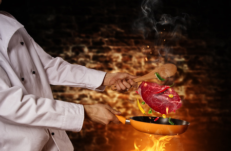 Closeup of chef preparing beef steak on grill pan, flying motion effect. Old brick wall on background