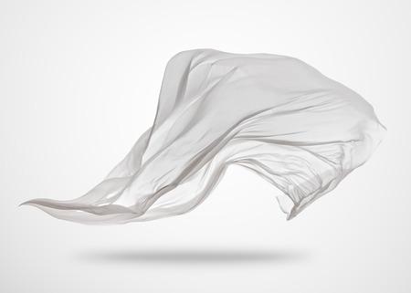 滑らかなエレガントな透明な白い布は、灰色の背景に分離。飛んでファブリックのテクスチャです。