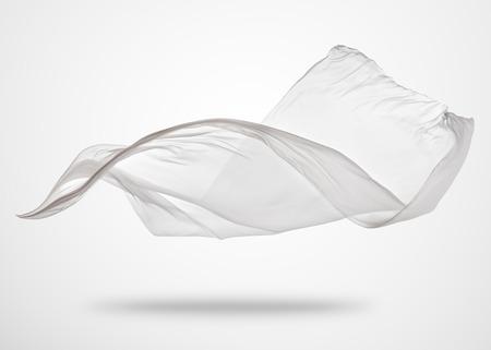 Glattes, elegantes, weißes Tuch auf grauem Hintergrund. Textur des fliegenden Stoffes.