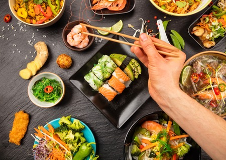 Man hand holding chopsticks and sampling asian food table with various kind of chinese food, noodles, chicken, pork, beef, sour soup, rice, spring rolls, sushi, prawns and many others. Served on black stone table, top view.
