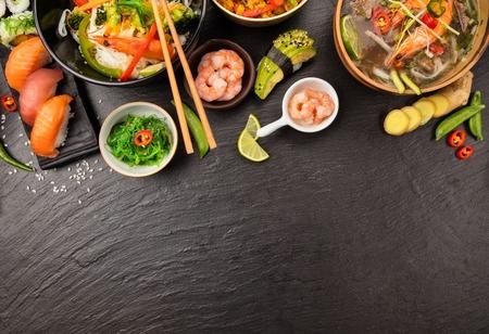 Mesa de comida asiática con varios tipos de comida china, fideos, pollo, sopa de gambas, arroz, sushi y muchos otros. Servido en la mesa de piedra negra, vista superior. Copyspace para el texto