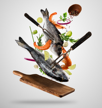 Flying raw whole bream fish and prawns, with ingredients for cooking. Freeze motion of cooking staff. Fork holding the meat. Concept of food preparation in low gravity mode. Separated on smooth gray background