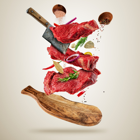 Flying pieces of raw beef steaks, with herbs, served on woodenboard. Meat chopper cuting the flesh. Concept of food preparation in low gravity mode. Separated on smooth gray background