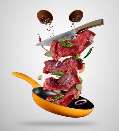 Volatili bistecche crude, con ingredienti per la cottura, dalla padella. Coltello che taglia la carne. Concetto di preparazione degli alimenti in modalità a bassa gravità. Separato su sfondo grigio Archivio Fotografico